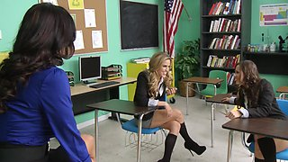 Two girls are getting fucked by their hot milf teacher in the class