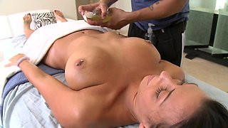 A woman is naked on the massage table, getting her tits massage