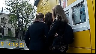 Three girls at the bus stop look at the dick